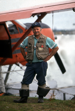 Alaska bush pilot Jim Hitch stands next to his classic Beaver float plane at Lake Hood
