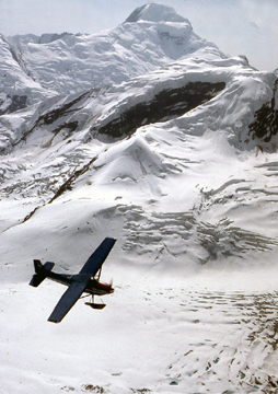 Glacier pilot Doug Geeting steers his plane by Mt. McKinley to drop off climbers at base camp