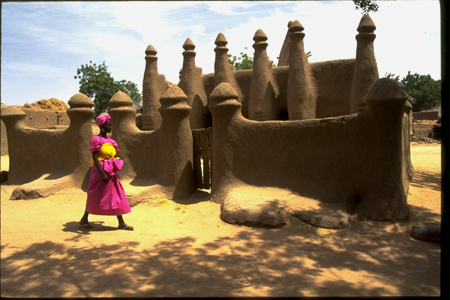 A Dogon woman walks past a mosque on the plain below the Bandiagara escaprpment in Mali. 