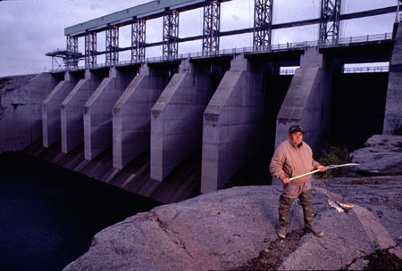 An Ojibwe elder holds a fishing net as he poses in front of the dam his tribe says threatens their subsistence life style